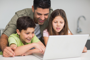 Father with young kids using laptop in kitchenの写真素材 [FYI00000406]