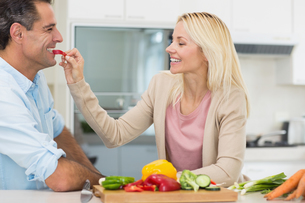 Happy loving woman feeding man vegetable in kitchenの写真素材 [FYI00000408]