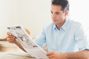 Serious casual man reading newspaper in kitchenの写真素材 [FYI00000409]