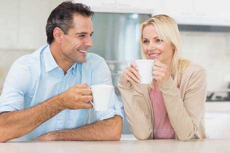 Happy couple with coffee cups in kitchenの写真素材 [FYI00000411]