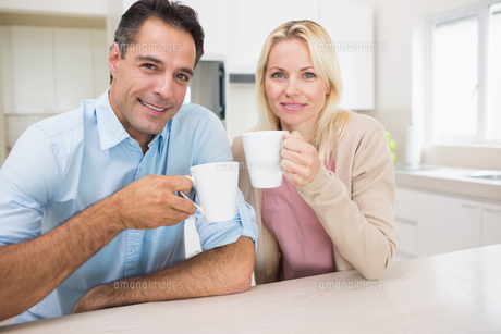 Portrait of happy couple with coffee cups in kitchenの素材 [FYI00000412]