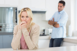 Thoughtful woman with blurred man in background in kitchenの写真素材 [FYI00000413]