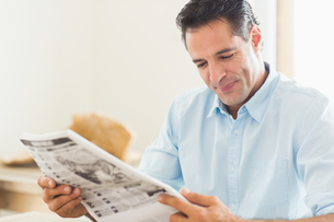 Smiling casual man reading newspaper in kitchenの写真素材 [FYI00000414]