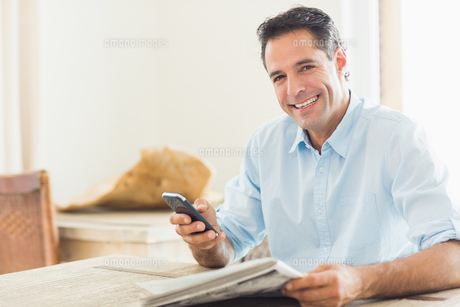 Smiling casual man with newspaper and cellphone in kitchenの写真素材 [FYI00000416]