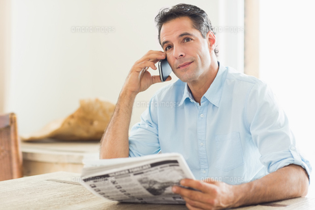Man with newspaper using cellphone in kitchenの写真素材 [FYI00000417]