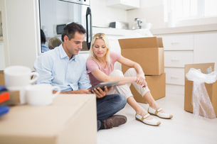 Couple using digital tablet amid boxes in houseの写真素材 [FYI00000418]