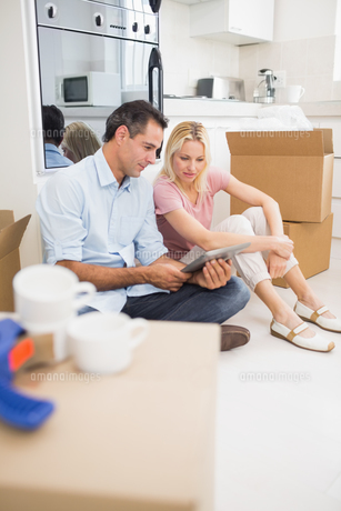 Couple using digital tablet amid boxes in houseの写真素材 [FYI00000420]