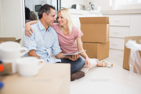 Couple using digital tablet amid boxes in a new houseの写真素材 [FYI00000422]