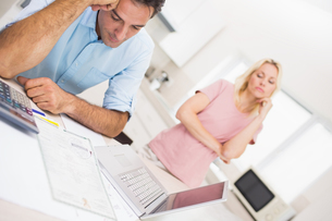 Worried couple with bills and laptop in kitchenの写真素材 [FYI00000423]