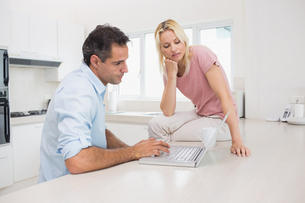 Concentrated couple using laptop in kitchenの写真素材 [FYI00000424]