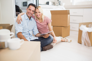 Couple using digital tablet amid boxes in new houseの写真素材 [FYI00000426]