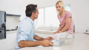 Serious couple with laptop sitting in kitchenの写真素材 [FYI00000428]