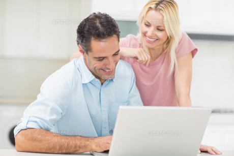 Happy couple using laptop in kitchenの写真素材 [FYI00000429]