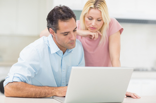 Concentrated couple using laptop in kitchenの写真素材 [FYI00000430]