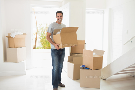 Smiling man carrying boxes in a new houseの写真素材 [FYI00000431]