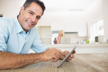 Portrait of smiling man using digital table in kitchenの素材 [FYI00000432]
