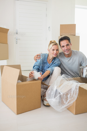 Smiling couple unpacking boxes in a new houseの素材 [FYI00000433]