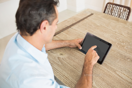 Concentrated man using digital table in kitchenの写真素材 [FYI00000434]