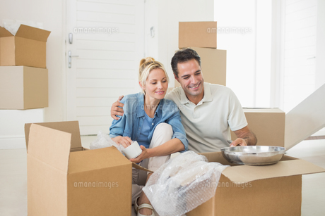 Smiling couple unpacking boxes in a new houseの素材 [FYI00000435]