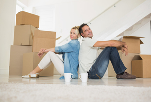 Smiling couple with cups and boxes in a new houseの写真素材 [FYI00000436]