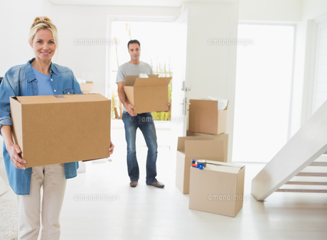 Smiling couple moving together in a new houseの写真素材 [FYI00000437]