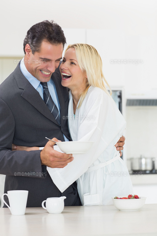 Cheerful woman embracing well dressed man in kitchenの写真素材 [FYI00000439]