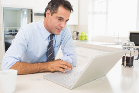 Concentrated well dressed man using laptop in kitchenの写真素材 [FYI00000440]