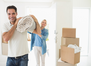 Smiling couple carrying rolled rug after moving in houseの写真素材 [FYI00000441]