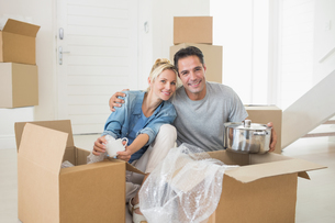 Smiling couple unpacking boxes in a new houseの写真素材 [FYI00000442]