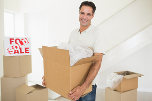 Smiling man carrying boxes in a new houseの写真素材 [FYI00000445]