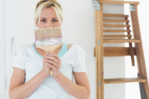 Woman holding paint brush in front of face at the new houseの写真素材 [FYI00000446]