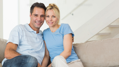 Portrait of a loving couple sitting on sofa in living roomの写真素材 [FYI00000447]