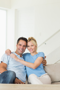 Portrait of a loving couple sitting on sofa in living roomの写真素材 [FYI00000450]