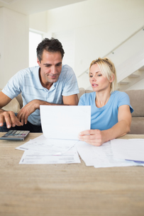 Concentrated couple with bills and calculator in living roomの写真素材 [FYI00000456]