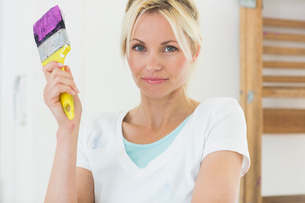 Beautiful woman holding paint brush in new houseの写真素材 [FYI00000457]