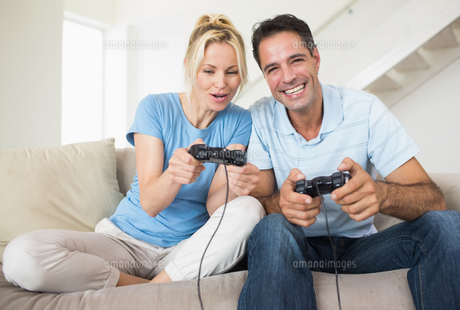 Cheerful couple playing video games in living roomの素材 [FYI00000459]