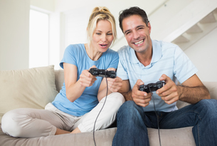 Cheerful couple playing video games in living roomの写真素材 [FYI00000459]