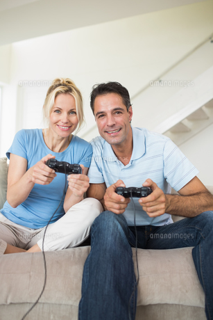 Cheerful couple playing video games in living roomの素材 [FYI00000464]