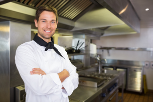 Smiling male cook with arms crossed in kitchenの写真素材 [FYI00000467]