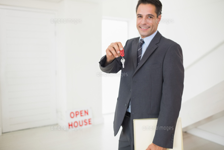 Businessman with documents holding up keysの写真素材 [FYI00000470]