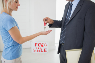 Real estate agent passing house key to womanの写真素材 [FYI00000471]