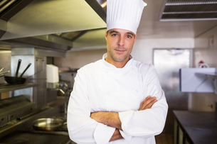 Male cook with arms crossed standing in kitchenの写真素材 [FYI00000472]