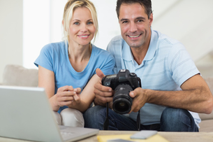 Happy couple with camera and laptop on sofa in living roomの写真素材 [FYI00000473]