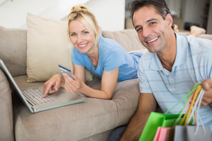 Portrait of smiling couple doing online shopping at homeの写真素材 [FYI00000474]