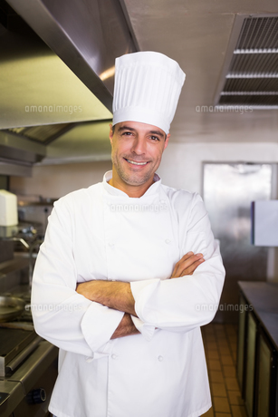 Smiling male cook with arms crossed in the kitchenの素材 [FYI00000475]