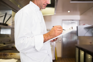 Concentrated male cook writing on clipboard in kitchenの写真素材 [FYI00000479]