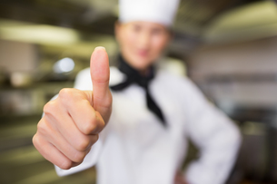 Blurred female cook gesturing thumbs up in kitchenの素材 [FYI00000480]