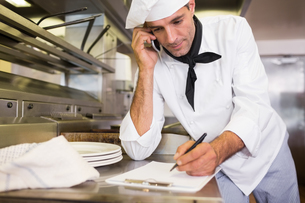 Cook writing on clipboard while using cellphone in kitchenの写真素材 [FYI00000482]