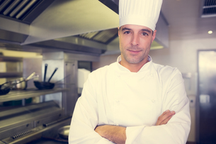 Smiling male cook with arms crossed in kitchenの写真素材 [FYI00000485]