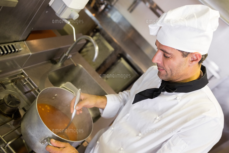 Concentrated chef preparing food in the kitchenの写真素材 [FYI00000488]